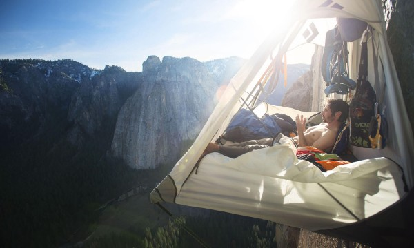 Climber Kevin Jorgeson examines his worn fingers as he rests in his portaledge on El Capitan's Dawn Wall